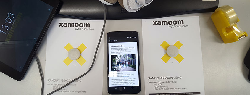 xamoom iBeacons on a desk with other office equipment
