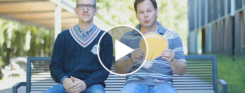 Bruno und Georg sitzen auf einer Bank und machen ein Video
