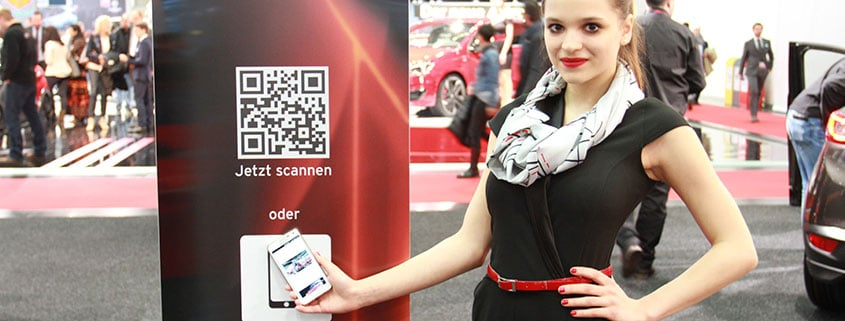 Woman holding a phone to a column equipped with QR and NFC