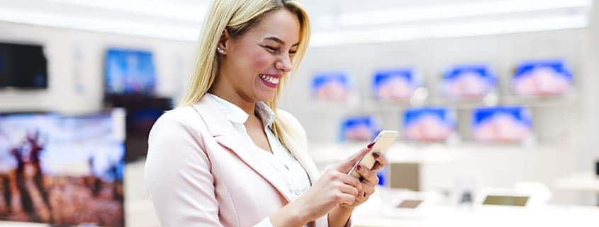 Woman laughing at her smartphone while shopping